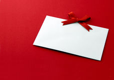Gift tag with red bow. White gift tag with red bow on red background Royalty Free Stock Photo