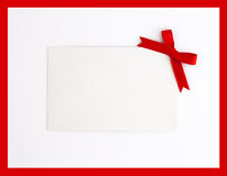 Gift tag with red bow. White gift tag with red bow on white background Stock Photos