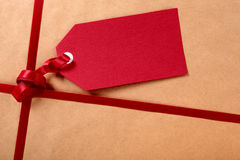 Gift tag and red ribbon, brown parcel wrapping paper background, copy space Stock Photos