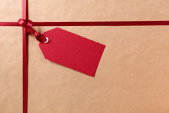 Gift tag and red ribbon, brown parcel wrapping paper background, copy space Stock Images