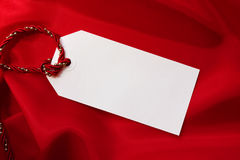 Gift Tag on Red Satin. Blank gift tag on folds of red satin, tied with red and gold festive cord Royalty Free Stock Images