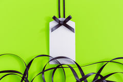 Gift tag with ribbon on green Royalty Free Stock Photography