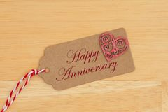 A gift tag on wood with a heart with text Happy Anniversary royalty free stock photos