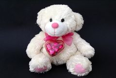 Gift of a teddy bear with a heart-shaped chocolate box Stock Photo