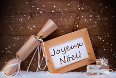Gift With Text Joyeux Noel Mean Merry Christmas, Snowflake, Snow. Christmas Card With Picture Frame On White Snow, Snowflakes And Christmas Gifts Or Presents Stock Photo