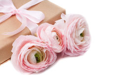 Gift tied with ribbon and pink flowers Stock Images
