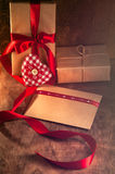 Gift tied with a ribbon and red heart from the tissues. In the box on wooden background. On Valentine's day Stock Photo