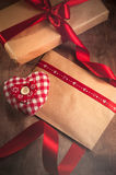 Gift tied with a ribbon and red heart from the tissues. In the box on wooden background. On Valentine's day Royalty Free Stock Photo