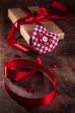 Gift tied with a ribbon and red heart. From the tissues in the box on wooden background. On Valentine's day Royalty Free Stock Image