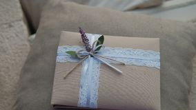 Gift in tissue package with delicate ribbon and flower lies on pillow in room. stock video footage