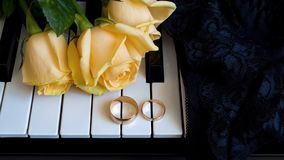 Gift to the beloved woman, yellow roses lie on the piano with engagement ring on black lace,lingerie, underwear on the wedding day royalty free stock images