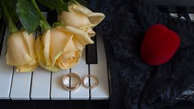 As a gift to the beloved woman, yellow roses lie on the piano with engagement ring and a red box in the shape of a heart on black stock photos