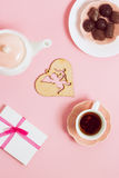 Gift to Valentine's Day, with tea and cupids on a pink background. Top view, film effect Royalty Free Stock Photos