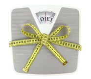 A gift to yourself. Bathroom scale with measuring tape bow Stock Photo