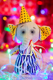 Gift toy elephant in cap stand on background of Christmas lights and boxes Royalty Free Stock Photo