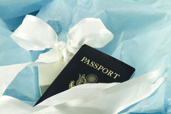 Gift of Travel, An Elegant Choice. A passport nestles in blue tissue paper accented by a white ribbon to reflect the elegant choice of travel as an enabling and Stock Photo