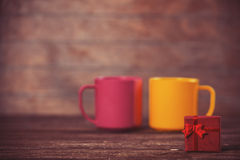 Gift and two cups. Little gift and two cups on background Stock Images