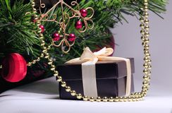 A gift under the green tree. Box for jewelry, with a beige ribbon, a nice gift for a woman in the New Year 2019 royalty free stock photography