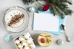 Gift voucher or greeting card on a marble table with a cup of cappuccino, dessert, meringue, vintage spoon,. Sprig of spruce and red clove stock photography