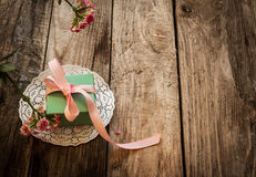 A gift on a white napkin. And flower on the wooden background Stock Images
