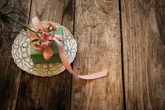 A gift on a white napkin. And flower on the wooden background Stock Photography