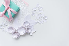 A gift on a white napkin. And white paper flowers Royalty Free Stock Photo