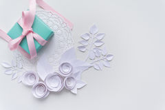 A gift on a white napkin. And white paper flowers Royalty Free Stock Photography