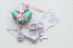 A gift on a white napkin. And white paper flowers Stock Photo