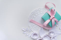 A gift on a white napkin. And white paper flowers Royalty Free Stock Images