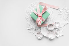 A gift on a white napkin. And white paper flowers Stock Photography