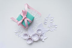 A gift on a white napkin. And white paper flowers Stock Images