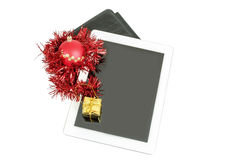 Gift white tablet with Christmas ball, box and red chain Stock Photos