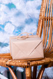 Gift on a wicker chair. Royalty Free Stock Images