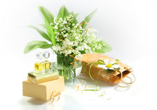 Gift for the woman he loved. Spring flowers, lilies and expensive perfume on a white background. Festive packaging bag yellow lies nearby stock photos