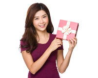 Gift woman in red smiling showing present Stock Photography