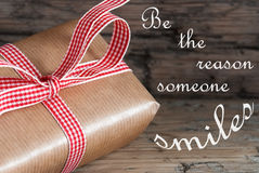 Gift. On wooden background saying be the reason someone smiles royalty free stock photo