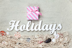 Gift and word Holidays with net and shells Royalty Free Stock Photos
