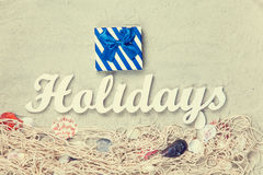 Gift and word Holidays with net and shells Royalty Free Stock Image