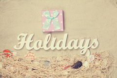 Gift and word Holidays with net and shells Royalty Free Stock Photography