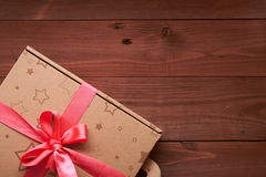 Gift wrap with a pink ribbon on a wooden table Stock Image