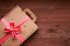 Gift wrap with a pink ribbon on a wooden table Stock Photos