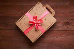 Gift wrap with a pink ribbon on a wooden table Royalty Free Stock Photography