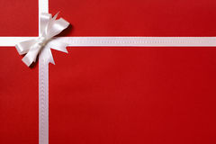 Gift wrap, white ribbon bow, red paper background, copy space Stock Image
