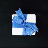 Gift wrapped in blue ribbon with polka dots Royalty Free Stock Image