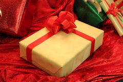 Gift Wrapped Christmas Present. Wrapped christmas present on red velvet like cloth Stock Images