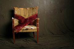 Gift wrapped dramatic chair. Gift wrapped vintage chair with dramatic lighting stock photos