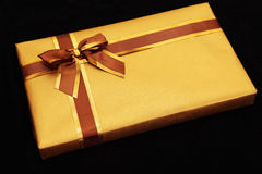 Gift wrapped in gold with brown/gold ribbon. Gift in gold wrapping paper against black Royalty Free Stock Photo