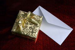 Gift wrapped in gold paper and blank envelope Stock Image
