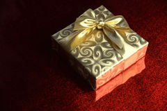 Gift wrapped in gold paper. On the red background Royalty Free Stock Images