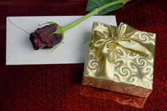 Gift wrapped in gold paper, red rose and a blank envelope Stock Image